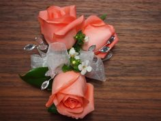 Traditional matching prom corsage and boutonniere using roses of peachy pink, highlighted with rhinestones, ribbons and filler.  www.urbanelementsinteriorspace.com Portland, OR