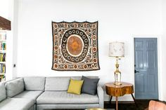 sectional, vintage textile, warm natural wood, white walls