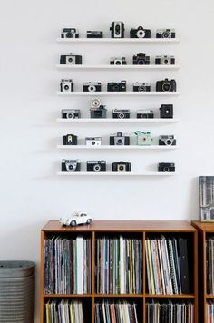 Camera collection can be displayed in various ways and one of the simplest and safest ways to display them is to arrange them neatly on a shelf in your living room. You can place them above a bookshelf or by the side of television to make it look neat. Also, when these cameras are placed in a shelf, it will be safe and you needn't worry about falling down or damage to it…