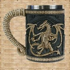 £5.00 off for 1 week only, while stocks last. A dragon skeleton on a gothic castle design covers this tankard and the handle has the appearance of spine bones. This dragon tankard has a removable stainless steel insert for ease of cleaning measuring approximately 12.5cms deep with a diameter of 8cms. The Dragon Remains Tankard brought to the Skulls and Dragons drinkware range by Nemesis Now.