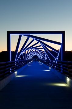 "High Trestle Trail Bridge: Arching over the decking are 43 steel ""cribbings,"" each lined with blue LED strips that come on at night—creating a must-see journey along the trail after dark. Walk through them, and you are bathed in the fluorescent glow; ride through them at 10 mph, and the lights spiral and blur together as though you're plunging deep into a mine or firing into warp drive."