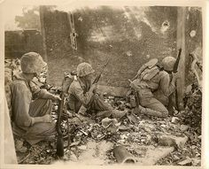 6th Division Marines Pinned Down in Okinawa Temporarily, during their fight among the wrecked homes and rubble of Naha, capital city of Okinawa island, Sixth Division Marines are pinned down by the fire of the Japs. They take cover behind a wall and one peers cautiously around the corner to see what is ahead of them. The first two on the left pack M-1 carbines , the third looking around the corner a Garand rifle.