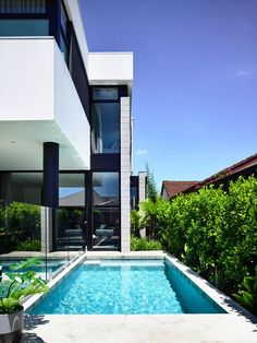 This modern house has a small swimming pool surrounded by lush plants and an alfresco dining area. #SwimmingPool