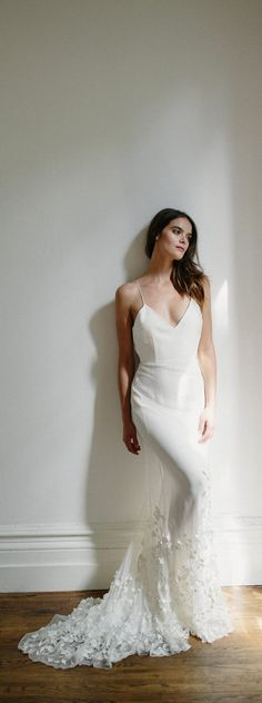 Elegant and exquisitely simple Alexandra Grecco mermaid wedding gown with plunging neckline, floral appliques on a beautiful tulle train and thin straps for the stylish, chic, au-naturale bride!