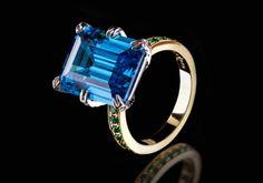 Das perfekt funkelnde Geschenk für romantische Seelen! Diesen handgemachten faszinierenden, rhodinierten und goldplattierten Ring mit einem grossen, dunklen Meerblauen Stein umgibt ein Kranz aus kleinen grünen Steinchen. Mini Steinchen in weiss zieren die obere Hälfte des Rings.  925er Sterling Silber 750er Gelbgold (18K) Vergoldung Rhodium überzogen Blaue Zirkonia, Smaragd Schnitt Zirkonia weiss Runde Grüne Kristall Steine Krappen Fassung