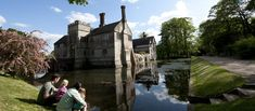 Visitors looking across the moat to Baddesley Clinton, Warwickshire