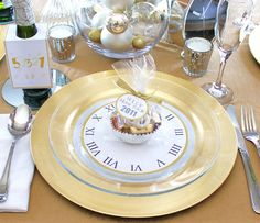 Gold and Silver New Year Table Setting:  Clock cut-outs below clear glass plates