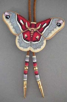 "Beaded Promethea Moth bolo by Todd Lonedog Bordeaux, Lakota  The subtle colors in Mr. Bordeaux's Promethea moth are truly enchanting. Leather backing; suede bolo cord with brass tips  4 1/2"" x 3""; 35"" cord  AOI00075 This is a special order item. For pricing and availability, please call 207 967-2122 or send us an email: admin@homeandaway.biz."