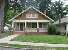 The front elevation is dominated by a substantial front gable that projects over a recessed porch. A rebuilt continuous brick foundation is interrupted by ...