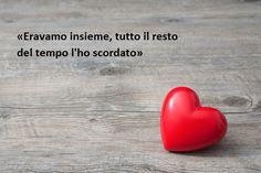 Frase famosissima sull'amore, immagine con un cuore rosso e uno sfondo effetto legno