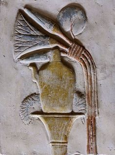 """This relief detail in the Inner Osiris Hall in the Seti I Temple at Abydos shows a """"nemset"""" vessel topped by lotus flowers. This kind of spouted vase was used to sprinkle water in purification rites. The detail is part of a relief in which Seti presents an emblem of Maat to Osiris. It is located on the north wall of the Inner Osiris Hall, between the entrances to the Horus Shrine and Seti Shrine (for an overall picture see photo 29913.) The Seti Temple at Abydos was begun by Seti I and…"""
