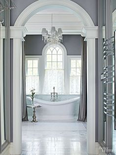 Deep door casings wrapped with substantial crown moldings preview the opulently layered woodwork that embellishes the bathing chamber's upper reaches. The archway perfectly frames a trio of windows (with the center window repeating the door's shape) and a statuesque soaking tub.