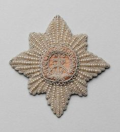 Star of the Order of St. Catherine Saint-Petersburg, second half of XVIIIth century. Pearls, silk, paper; embroidery Diameter 98 mm Belonged to Catherine the Great. Aquired from the palaсу property in 1922.