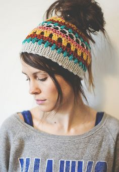 Whip up this crochet messy bun hat using your scraps of yarn for a stylish winter look.