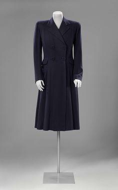 Wollen mantel met visgraatmotief ontworpen door Henriette Boudreau. De snit van deze mantel van donkerblauwe wol met visgraatmotief is vrij sober en doet denken aan die van mannenjassen; dit is ook te zien in de vorm van de kraag. Dit soort halflange getailleerde damesmantels, werd in modebladen tot in de jaren 1940 redingote genoemd naar hun 18de-eeuwse voorgangers | Rijksmuseum | ca. 1930-1940