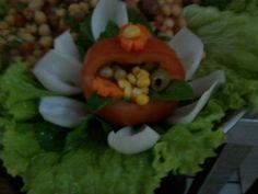 uma flor de cebola e uma cestinha de tomate, com salada de grão de bico