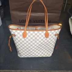 "Louis Vuitton Neverfull mm tote This is an authentic LOUIS VUITTON Monogram  Damier Azur Neverfull MM.   Measurements: 17""L x 6""W x 11.5""D --8.5"" Drop  Item Condition: Gently used.  Monogram canva  and  All 4 corners are in great shape.Trim leather has few minor marks.overall  Interior is clean with few makeup marks.  Goldtone hardware is nice and shiny. Handles and trim are turning patina.  I included very detailed pictures and gave accurate written descriptions- please check them…"