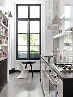Compact kitchen, shelving, lighting, black windows