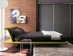 Już na pierwszy rzut oka widać, że lokator tej sypialni ceni komfort i poczucie przytulności. Włochaty dywan na podłodze czy wykończenie ścian przy użyciu drewnianej sklejki – wszystko to buduje nastrojowy klimat wnętrza. Przesuwne drzwi szafy tworzą spójną całość ze ścianą.