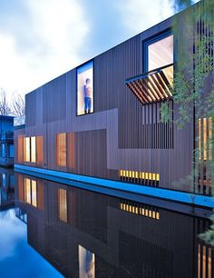 Slatted-timber siding covers the exterior of Framework Architecten and Studio Prototype's Water Villa, a house that rests in a canal southwest of Amsterdam's city center, close to the stadium built for the 1928 Summer Olympics. The three-level residence encompasses 2,690 square feet, and the interior features sleek hallways, an all-white kitchen, and a spacious living area. Sunlight streams into the home through the exterior slats and a skylight above the atrium. The design allows the…