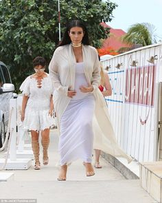 Another beach day: Kim Kardashian was spotted keeping a protective hand on her pregnant stomach while heading to the beach with her family in St Barts as Kris Jenner followed close behind on Wednesday