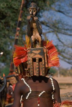 Africa | A Malian wears a mask incorporating the figure of a monkey at the performance of a ritual dance. Pays Dogon, Mali. | Image and caption © Charles & Josette Lenars