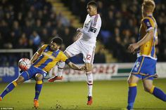 Manchester United defender Chris Smalling (centre) scuffs his effort but the ball ended up in the back of the Shrewsbury net