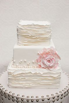 Mix-And-Match Patterns  Simple pearl drops and a bold rose on the center tier perfectly breaks up this textured cake.