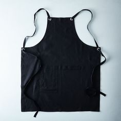 "$76 Black Cross-Back Kitchen Apron with Black Ties on Food52. Made of: Apron is 100% black linen; straps are cotton twill; nickel-plated grommets Size: One size fits most; Apron is 30"" W and 35"" L when laid flat. Bib is 10"" W at top and gradually increases to waist. Straps are approximately 60"" L with plenty of room to adjust. Sourced from: Studiopatró"