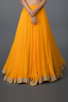 Perfect for Wedding Haldi, Mehandi and Sangeet events, this yellow tilla aari embroidered leheriya lehenga outfit is sure to turn heads. The handcrafted pure georgette leheriya lehenga skirt and dupatta is adorned with silver tilla aari embroider Indian Gowns Dresses, Indian Fashion Dresses, Dress Indian Style, Indian Designer Outfits, Designer Dresses, Indian Outfits, Indian Wear, Lehenga Saree Design, Lehenga Designs