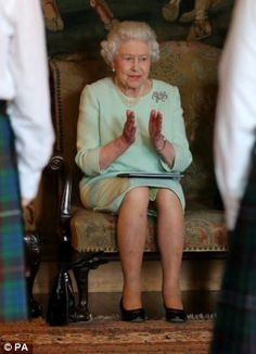 Queen Elizabeth II, who is Patron of the Royal Country Dance Society, watches a performance from The Royal Country Dance Society  whilst staying at holrood house for her annual week of events in scotland