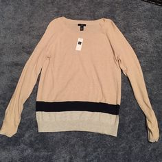 Gap light weight sweater. Tan sweater with navy and grey stripes at the bottom. Perfect for any occasion. Never worn, tag still on. Wasn't my size and has just sat in my closet. GAP Sweaters Crew & Scoop Necks