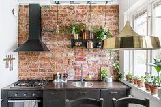 Precioso frontal de cocina con pared de ladrillo visto y lámpara colgante en dorado.