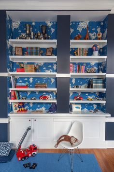 A Stately Victorian Where Family-Friendly Meets Formal: World map wallpaper lines a built-in bookshelf in a blue and white kids room.
