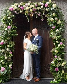 Laura and John under a beautiful floral arrangement by Amanda in Abbey Florists Floral Wedding, Wedding Flowers, Floral Arch, Florists, Bridesmaid Dresses, Wedding Dresses, Floral Arrangements, Amanda, Wedding Venues