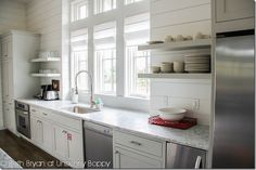 White plank siding walls, open shelving, pristine grey/blue cabinetry, marble countertops, stainless appliances, and they even had my favorite Duralex picardie tumblers stacked oh-so-perfectly in giant window filled spaces
