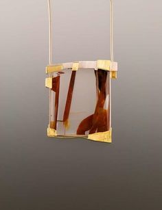 """""""Portal"""" pendant by Eleanor Moty, 2007. Sterling silver, 22K gold, sapphire, quartz with iron oxide inclusions (Dieter Lorenz, Lapidary artist, Germany)."""
