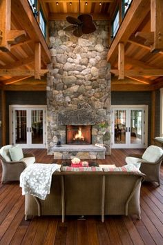 A covered deck with large river stone fireplace as a focal point.