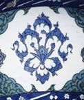 Mosque lamp, made of polychrome glazed pottery. The lamp has a pyriform body with three applied ear-shaped handles and a moulding at the juncture with the trumpet neck, on a spreading profiled foot.  It is painted in tones of cobalt blue and grey-green outlined in black with chinoiserie cloud bands alternating with small arabesque knots between pointed green-ground half-cartouches filled with black scrollwork.  A similar design is repeated on the neck.  Inscription bands of differing width…