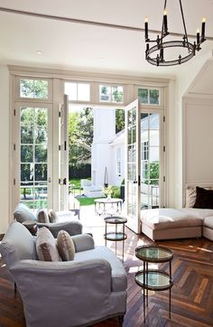 Richard Shapiro - Gwyneth Paltrow - Bright and open living room with French doors with transom windows leading to courtyard. Gorgeous living space with iron candelabra in vaulted ceiling and herringbone hardwood floors. Pale gray slipcovered armchairs paired with lilac velvet pillows, linen sectional sofa and antique brass end tables.