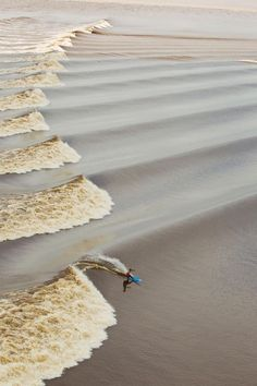 Tidal Bore    A tidal bore is a tidal phenomenon in which the leading edge of the incoming tide forms a wave (or waves) of water that travels up a river against the direction of the river's current.    In this photo, Tom Curren chases mesmerizing waves on the Seven Ghosts tidal bore, deep in the heart of the Indonesian jungle into the first legitimate river bore barrels in history.    Photo © 2011 Nate Lawrence