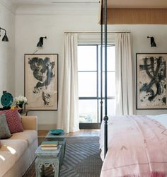 love the couch facing the foot of the bed and the art framing the window.