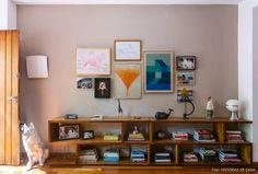 Sala de estar tem aparador de madeira com muitos livros e parede galeria com quadros e fotos de família.