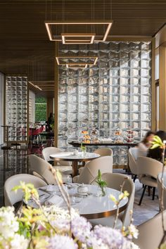 Restaurant at The Murray hotel in Hong Kong, which sits within the shell of a gridded 1960s tower once used as governmental offices. Now completed by Foster + Partners. The gold shimmer on the finishes is achieved with PVD coloured stainless steel (Double Stone Steel)