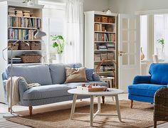 """Ein helles Wohnzimmer im traditionellen Stil u. a. mit STOCKSUND 3er-Sofa mit Bezug """"Remvallen"""" blau/weiß und hellbraunen Holzbeinen"""