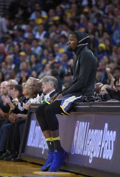 Kevin Durant of the Golden State Warriors looks on while sitting on the scorers table against the San Antonio Spurs during an NBA basketball game at...