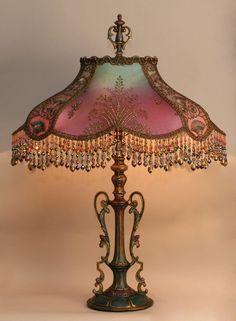 Античный эпохи 1920-х годов металла лампа база была ручная роспись и держит руку окрашенные шелковые абажуры турецкой Старлинг.  Тени Ombre окрашенный от бледно-бирюзовые в глубокий лиловый.  Тени покрыта по бокам с золотой металлик с бирюзовой чистой сучки.  Передние панели покрыты изысканно подробную золото бисером металлической сеткой.  Небольших панелей украшены красивыми модерн / Египетский стиль расшитые золотом сеткой.  Викторианской эпохи и синели металлической отделкой корону…