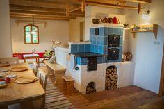 Modrý kachlový sporák se dvěma troubami. Krásný dřevěný interiér a chalupa v Bilých Karpatech.