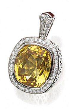 FANCY COLORED SAPPHIRE AND DIAMOND PENDANT. The cushion-shaped sapphire of yellow-orange color weighing 42.11 carats, bordered by 49 round diamonds weighing approximately 1.25 carats, mounted in platinum.