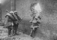 Convenient: British foot soldiers pass through a hole in a wall, which handily has been blasted out for them by a previous shell. Few cameras were on the front line